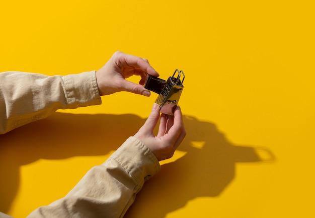 As mãos seguram o chocolate e o ralador na superfície amarela