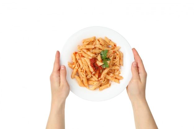 As mãos seguram o prato com macarrão saboroso, isolado na parede branca