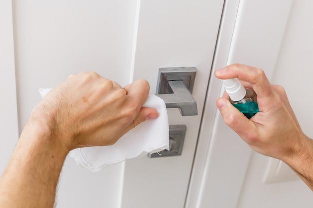 As mãos seguram o pulverizador com um anti-séptico, a outra - limpa a maçaneta da porta com um pano umedecido com uma solução desinfetante