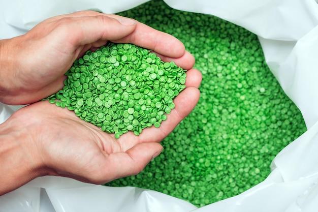 As mãos seguram ou tocam pelotas de plástico biodegradáveis, grânulos de corante de polímero plástico de cor verde claro