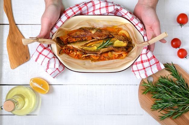 As mãos seguram peixes recém-cozidos. legumes, ervas aromáticas, azeite de oliva em uma mesa de madeira branca. vista do topo