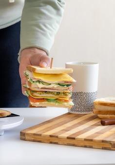 As mãos seguram um sanduíche fresco cozido com queijo, bacon e uma xícara de café ou chá de vegetais