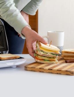 As mãos seguram um sanduíche fresco cozido com queijo, bacon e vegetais perto da toster e xícara de café