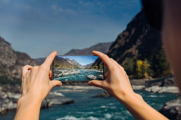 As mãos seguram um smartphone e tiram foto do rio da montanha e pedras