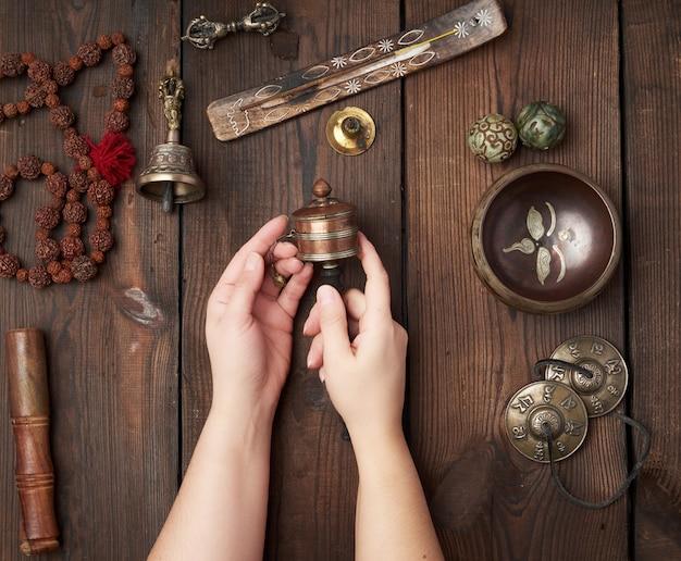 As mãos seguram um tambor de oração na mesa de madeira