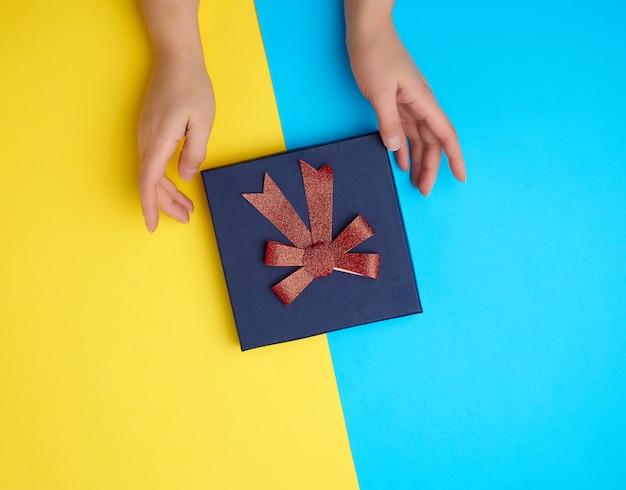 As mãos seguram uma caixa de papelão fechada com um laço vermelho