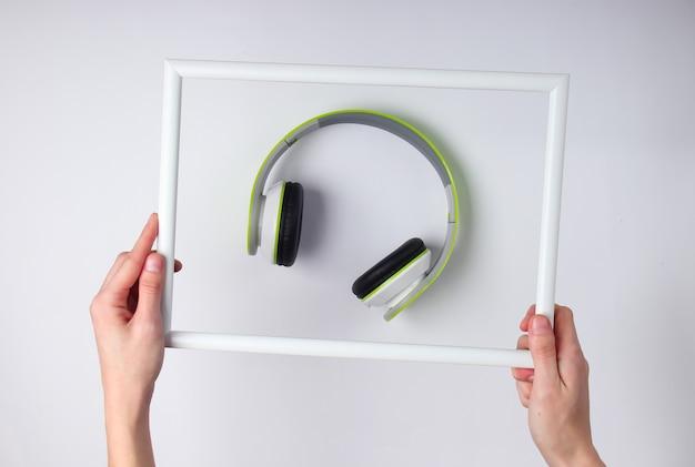 As mãos seguram uma moldura branca com fones de ouvido estéreo em uma superfície branca