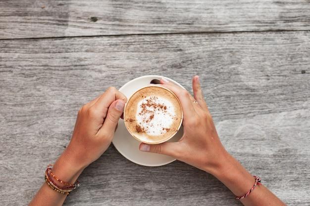As mãos seguram uma xícara de café.