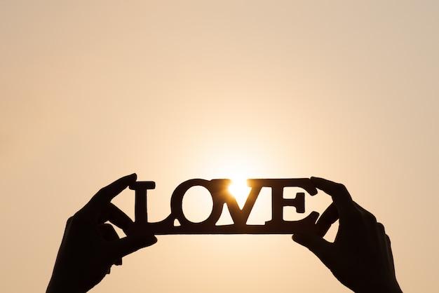 As mãos segurando a palavra amam no fundo por do sol. conceitos de amor.
