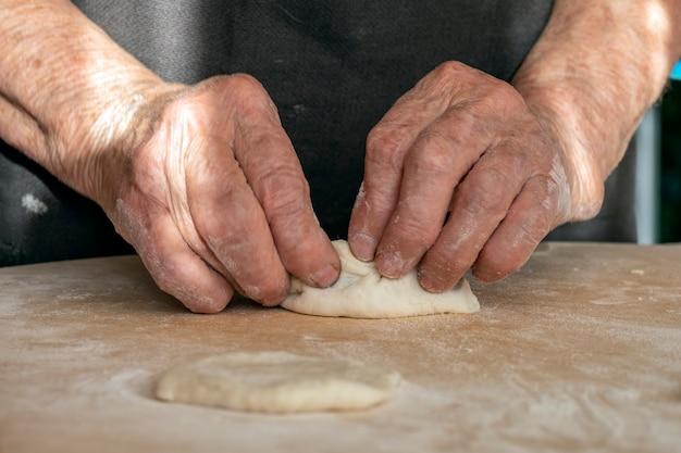 As mãos sobrecarregadas da velha estão fazendo tortas de massa