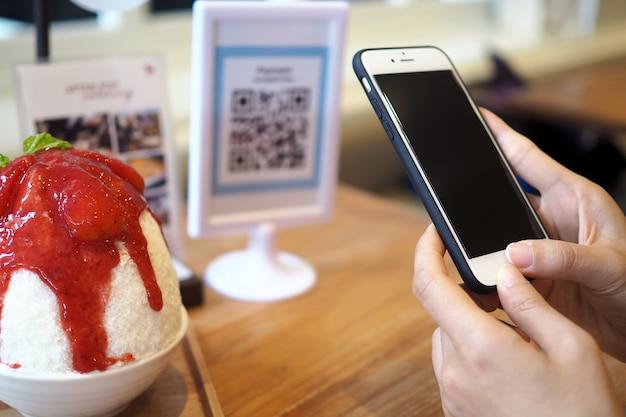 As mãos usam o telefone para escanear o código qr para receber descontos dos pedidos do binsu no café.
