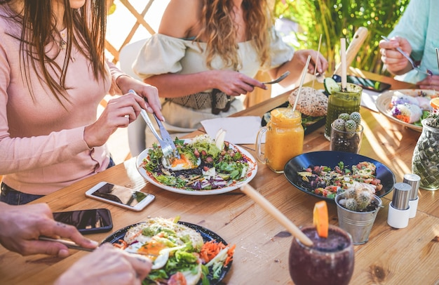 As mãos vista de jovens comendo brunch e bebendo batidos tigela com canudos ecológicos no moderno restaurante bar. estilo de vida saudável, conceito de tendências alimentares