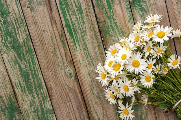 As margaridas da camomila de campo do ramalhete florescem no puxador da porta no fundo de madeira velho.