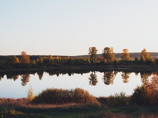 As margens, o céu e as árvores são refletidos na superfície da água. lago na temporada de outono. Foto Premium