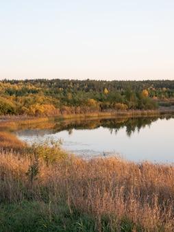 As margens, o céu e as árvores são refletidos na superfície da água