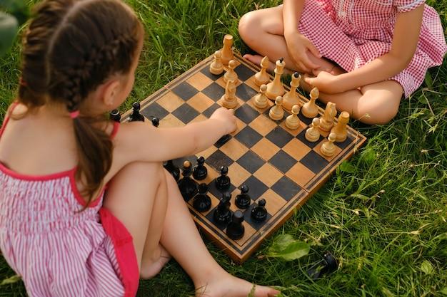 As meninas aprendem a jogar xadrez no jardim em um velho tabuleiro de xadrez