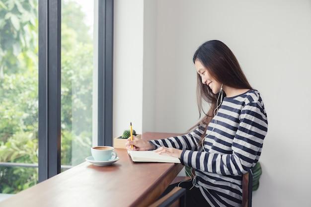 As meninas asiáticas estão tomando notas e ouvindo música em uma cafeteria.