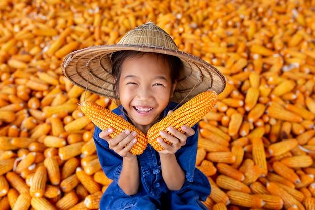 As meninas asiáticas prendem o milho entre o milho para o alimento.