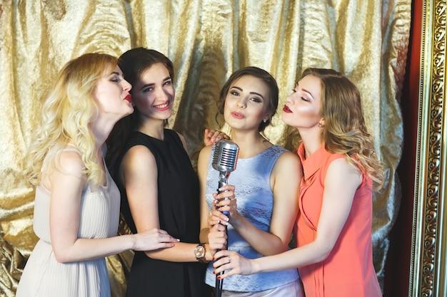 As meninas cantam karaokê no restaurante.