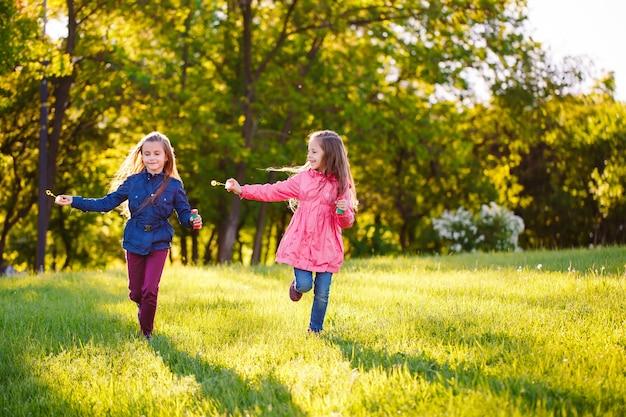 As meninas correm e brincam com bolhas de sabão.