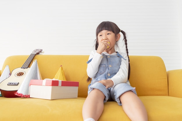 As meninas de crianças bonitos alegres comem a maçã perto do presente atual na sala de visitas branca.