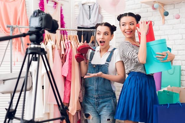 As meninas do blogger apresentam bolsas coloridas e sapatos vermelhos.