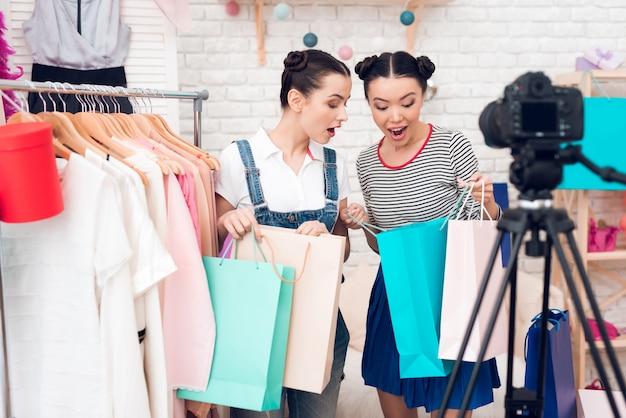 As meninas do blogger apresentam muitas bolsas coloridas para a câmera