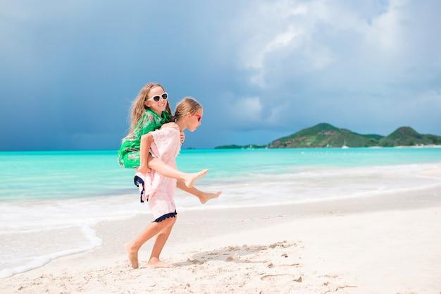 As meninas engraçadas felizes pequenas têm muito divertimento na praia tropical que jogam junto.