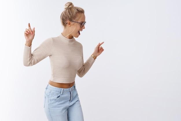 As meninas enlouquecem. foto interna de uma jovem elegante e despreocupada dançando, virando à direita, levantando as mãos e acenando ao som de boa música, curtindo a festa se divertindo contra um fundo branco