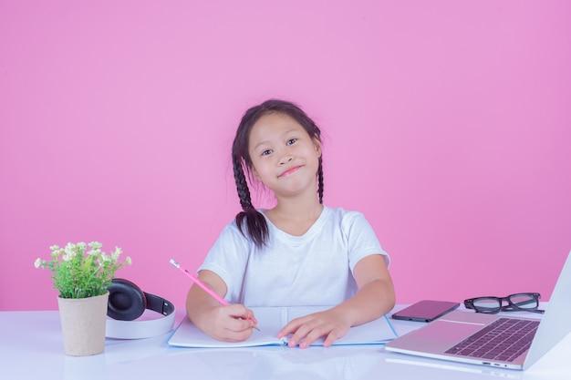 As meninas escrevem livros sobre um fundo rosa.
