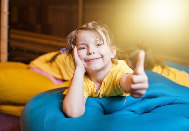 As meninas estão deitadas no saco da cadeira com os polegares levantados no centro infantil