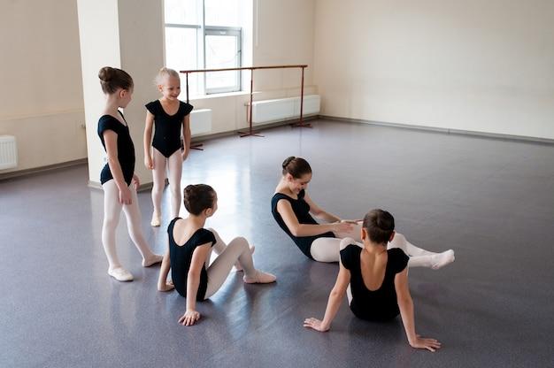 As meninas estão envolvidas em coreografia na aula de balé.