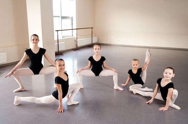 As meninas estão envolvidas na coreografia na aula de balé.