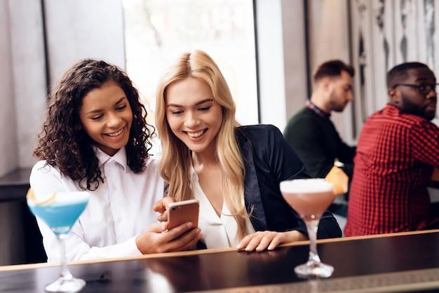 As meninas estão olhando para a tela de um telefone celular.