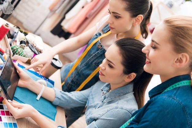 As meninas estão olhando para um tablet em uma fábrica de roupas.