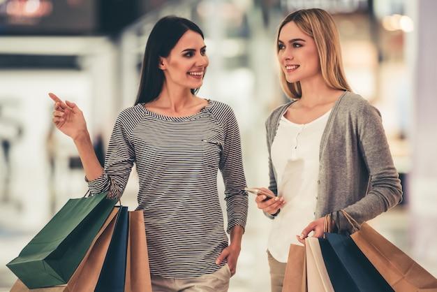 As meninas estão sorrindo enquanto fazia compras no shopping