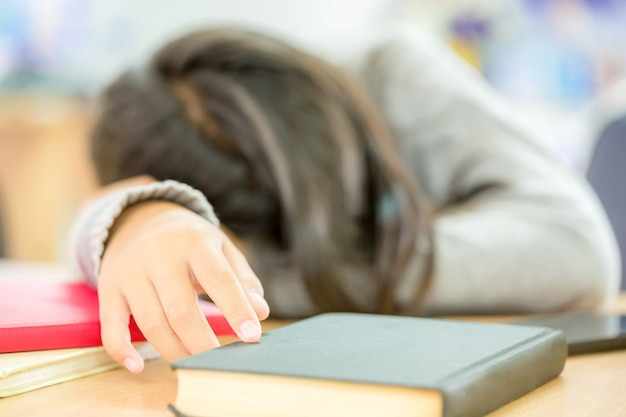 As meninas estão tirando uma soneca enquanto lê livros