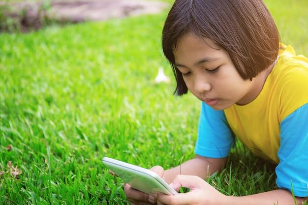 As meninas estão usando o tablet no gramado.