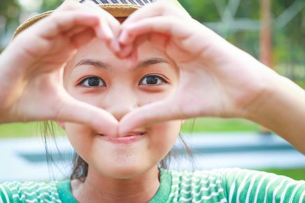 As meninas fazem as mãos, em forma de coração, cruzam os dedos.