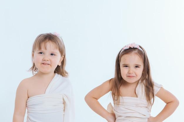 As meninas fazem caretas contra um fundo branco. as crianças estão tramando algo. conceito de emoções, expressões faciais, infância, sinceridade