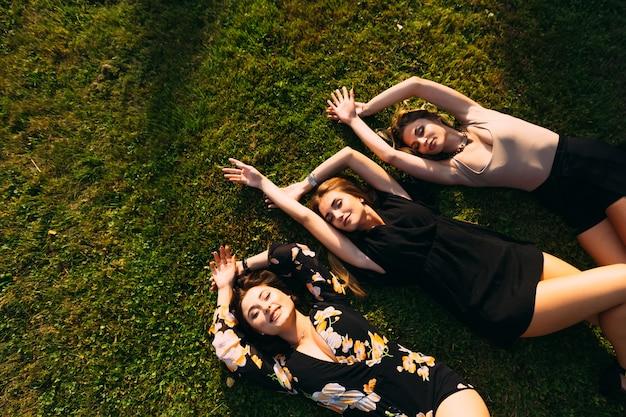 As meninas fecharam os olhos e deitaram na grama