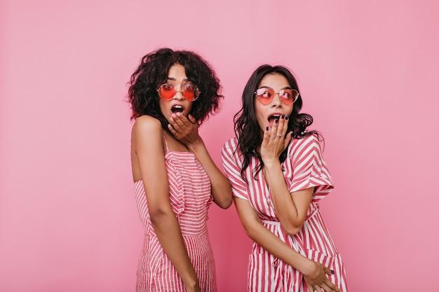 As meninas ouvem um segredo terrível e cobrem a boca de surpresa. senhoras de pele escura com óculos legais.