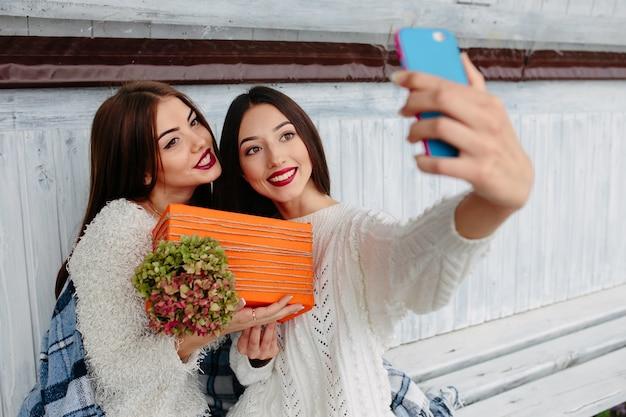 As meninas que tomam uma foto com um telefone celular azul e um presente de laranja