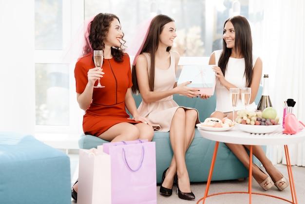 As meninas se sentar no sofá com uma taça de champanhe.