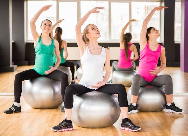 As meninas sentam-se em bolas e fazem exercício.