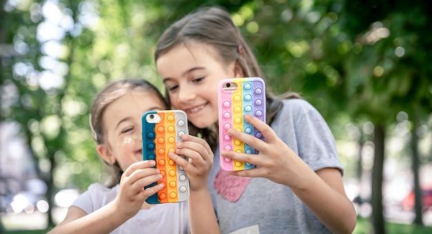 As meninas usam telefones em estojos da moda para anti-stress pop it.