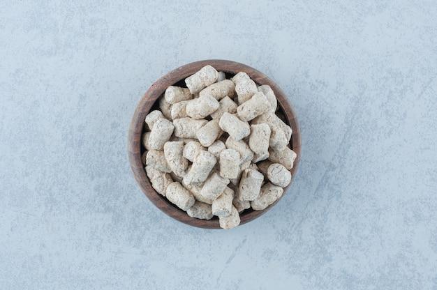 As migalhas de pão na tigela ao lado do espigão no mármore.