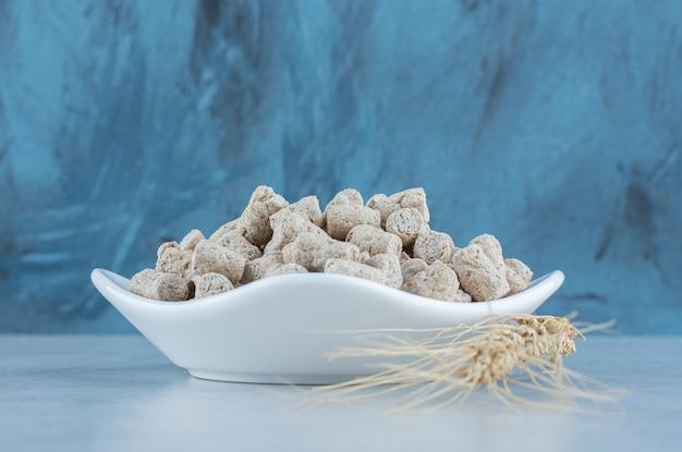 As migalhas do biscoito na tigela ao lado do cravo no mármore.