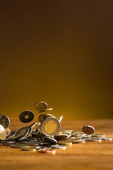 As moedas de prata e ouro e moedas caindo na mesa de madeira