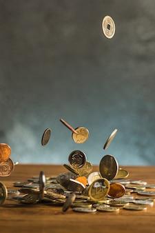 As moedas de prata e ouro e moedas caindo na parede de madeira